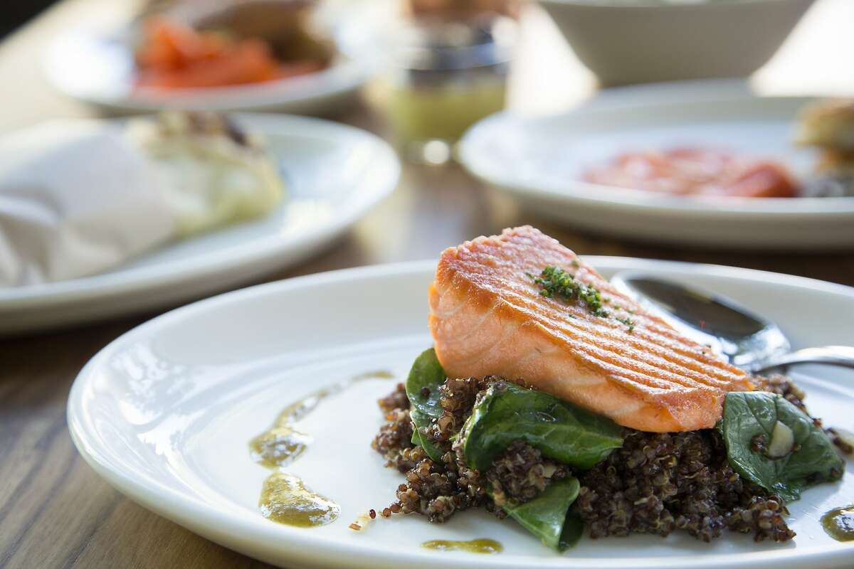 A salmon dish with quinoa, olives, almonds, wilted spinach and lemon scallion vinaigrette at Little Gem