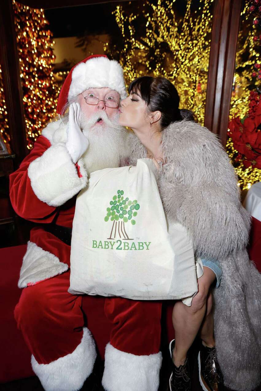 Santa and actress Selma Blair pose at the Baby2Baby holiday event at The Grove on Dec. 16, 2015 in Los Angeles.