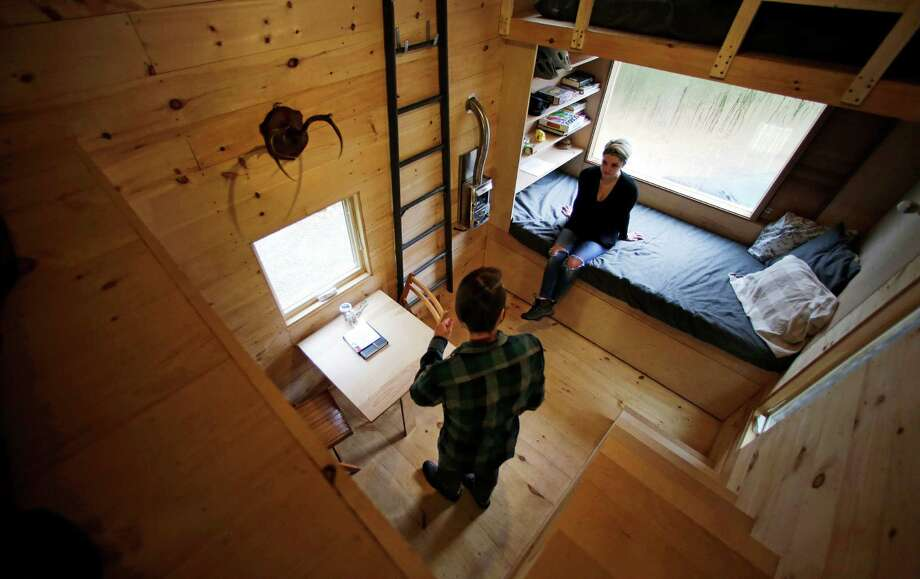 FILE - In this Oct. 20, 2015 photo, Shane Lentz, of Pittsburgh, Pa., and his wife Hilary, talk before leaving a tiny house, which they rented for a weekend, in Croydon, N.H. According to Thetinylife.com, the typical U.S. home is about 2,600 square feet. The typical tiny house is 100 to 400 square feet.  (AP Photo/Charles Krupa, FIle) Photo: Charles Krupa, STF / AP