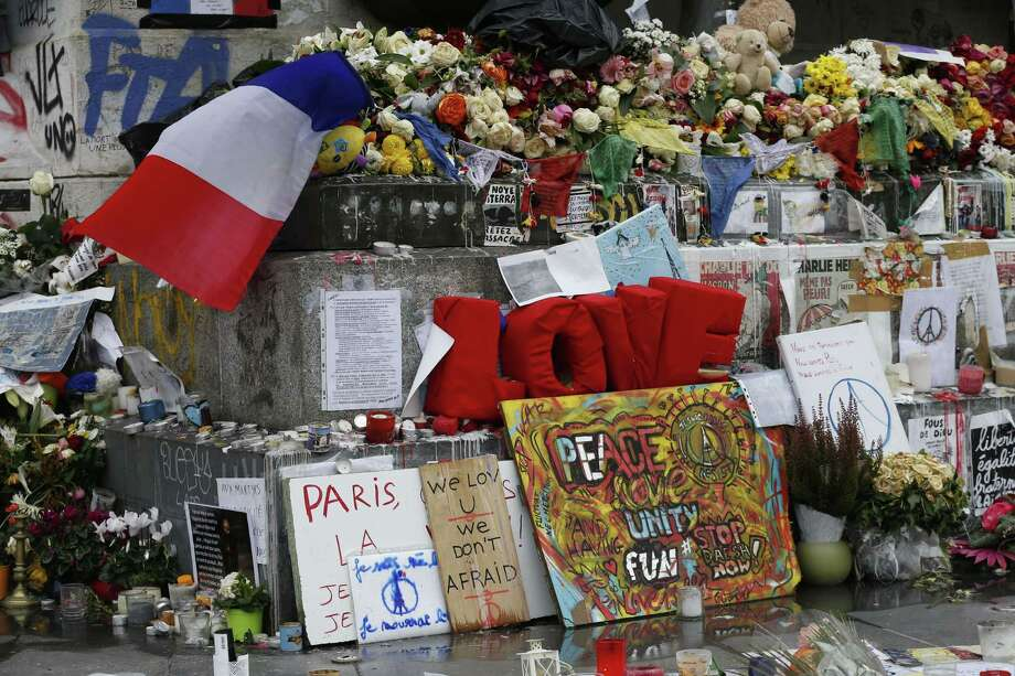 A picture taken on November 27, 2015, shows French national flags, candles and flowers at a makeshift memorial in Place de la Republique square in Paris, for the National Tribute to the 130 people killed in the November 13 Paris attacks. Photo: THOMAS SAMSON / AFP