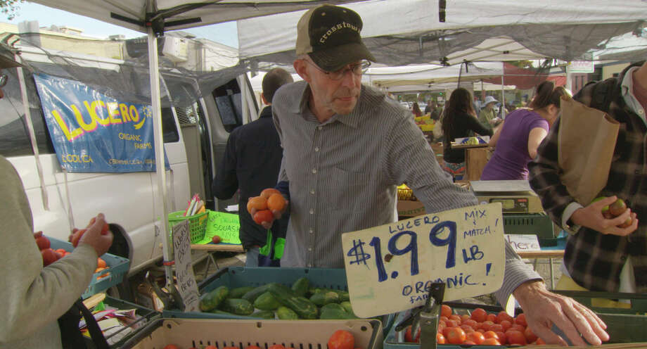 """Michael Pollan at a farmers' market. His advice: """"Eat food. Not too much. Mostly plants."""""""