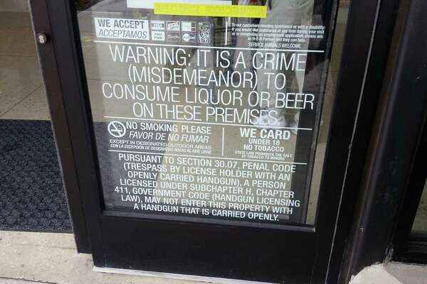 A sign on the door of the H-E-B South Flores Market barring customers from entering with open-carry handguns.