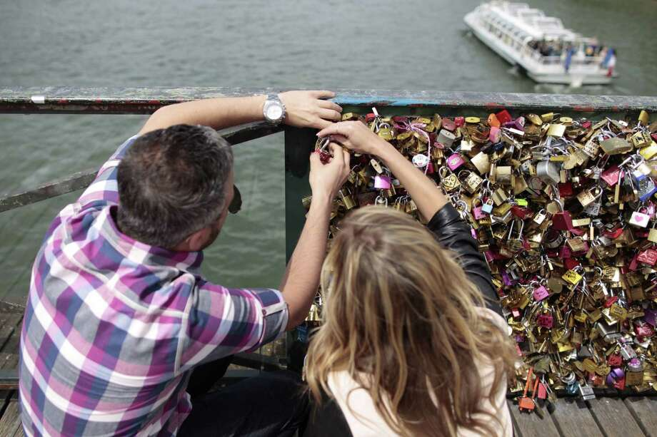 """Though city workers in Paris removed about 700,000 """"love locks"""" weighing a combined 45 tons from the Pont des Arts bridge, it didn't stop anyone from adding more. Photo: CHARLY TRIBALLEAU, Stringer / AFP"""