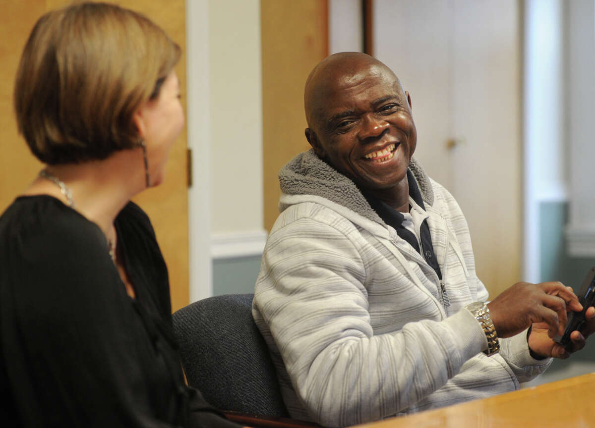 Congolese refugee Thomas Kitoko laughs with iiconn President and CEO Claudia Connor during a meeting at the institute in Bridgeport, Conn. on Wednesday, December 23, 2015.
