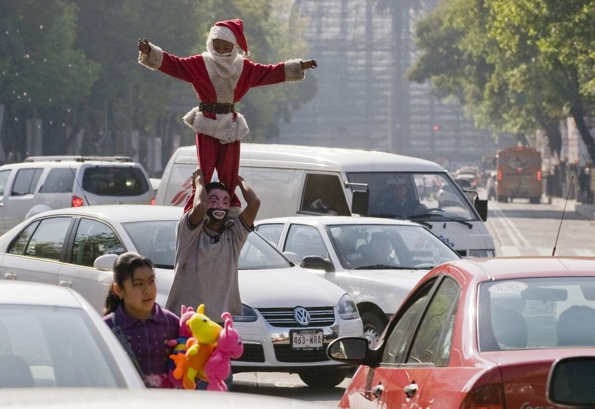 Street performer Santa A child dressed as Santa Claus performs a balancing act at the Reforma Avenue in Mexico City, on December 22, 2009.