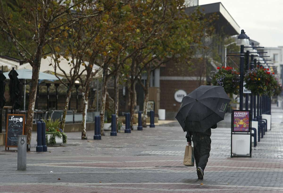 Keith DuBay walks back home through the rain at Jack London Square in Oakland, Calif. on Thursday, Dec. 24, 2015.
