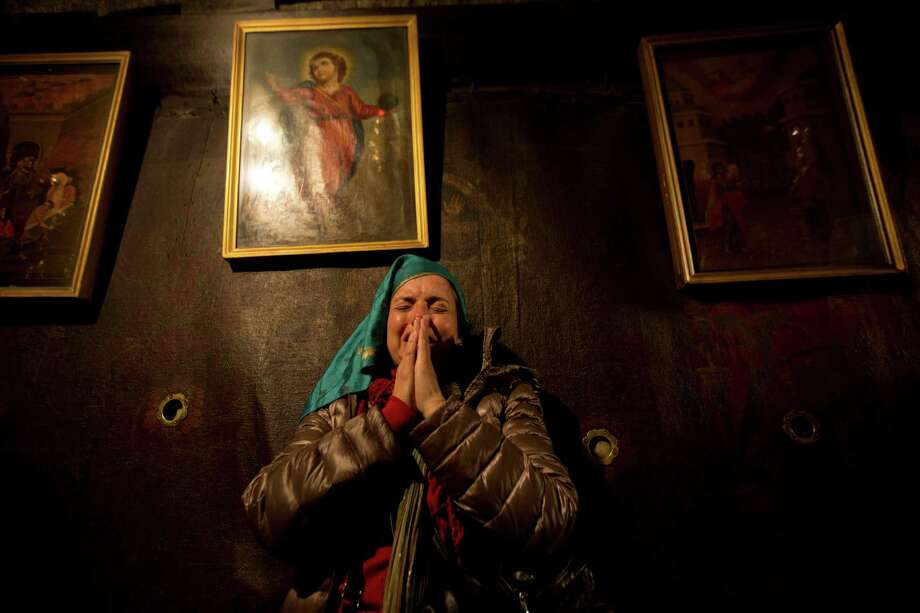 Christian pilgrims pray inside the Grotto of the Church of Nativity, traditionally believed by Christians to be the birthplace of Jesus Christ, in the West Bank town of Bethlehem on Christmas Eve. Photo: Majdi Mohammed, STF / AP