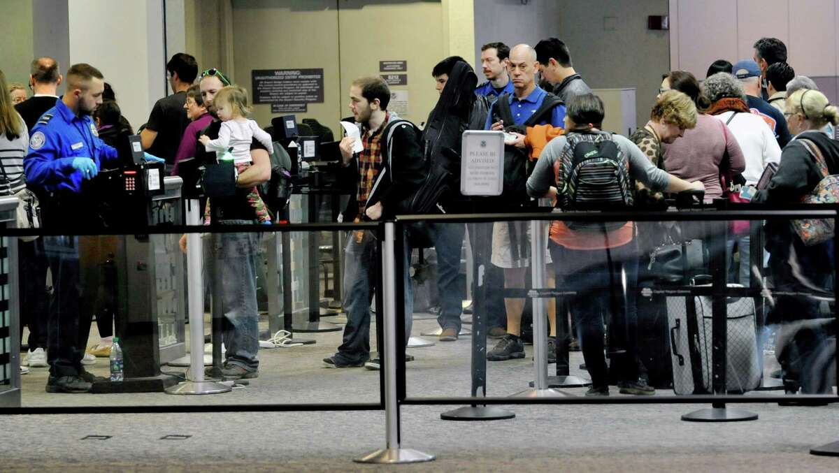 Travelers make their way through the security checkpoint before flying out at the Albany International Airport on Thursday, Dec. 24, 2015, in Colonie, N.Y. (Paul Buckowski / Times Union)