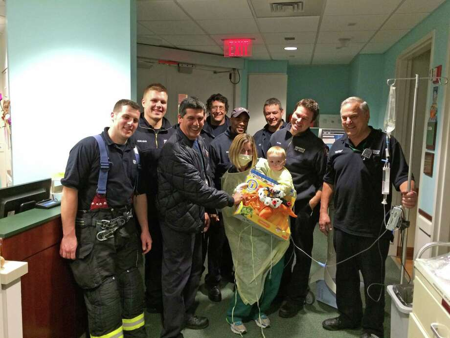 Kristen Cioffi, RN, held seven-month-old Lucas to greet the fire fighters who donated toys to Pediatric Specialty Center at Greenwich Hospital. Members of Greenwich Fire Fighters Local 1042, Group 3, delivered $700 worth of toys to the Pediatric Specialty Center at Greenwich Hospital. Most of the toys were purchased at North Street Pharmacy in Greenwich. Sonali Costa, pharmacist and owner, was so moved by the effort that the store donated about $200 worth of toys to the hospital. Some of the firefighterís children donated gifts, too. Photo: Contributed / Contributed Photo / Greenwich Time Contributed
