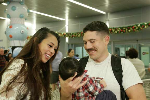 CJ Patlan, right, a Marine stationed in Okinawa, Japan, meets his son Raphael for the first time as his wife Roxanne watches at Bush IAH Airport Thursday, Dec. 24, 2015, in Houston.