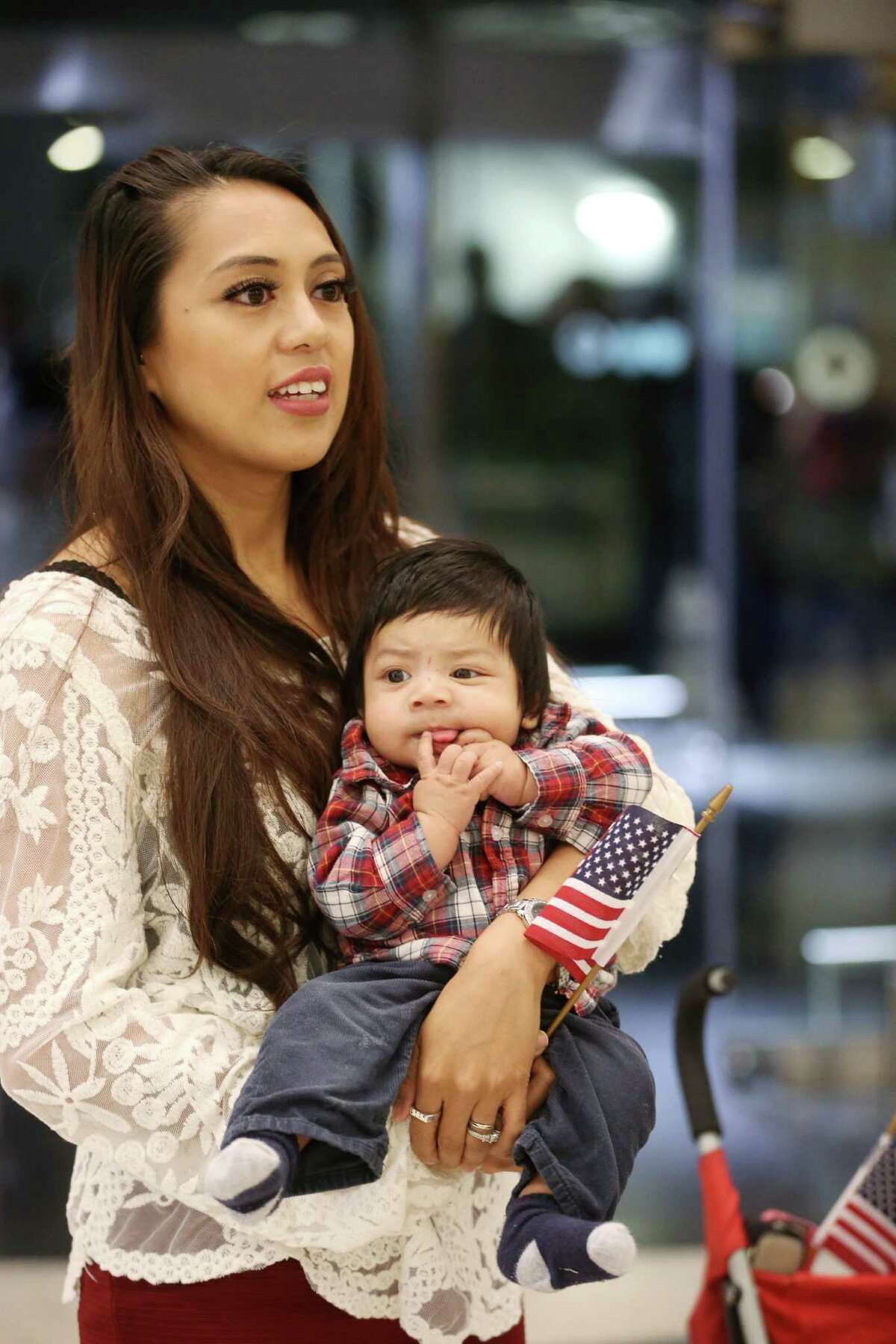 Roxanne Patlan waits with her son Raphael for her husband CJ at Bush IAH Airport Thursday, Dec. 24, 2015, in Houston. Patlan's husband is a Marine stationed in Okinawa, Japan, whose flight home was paid for by a GoFundMe campaign.