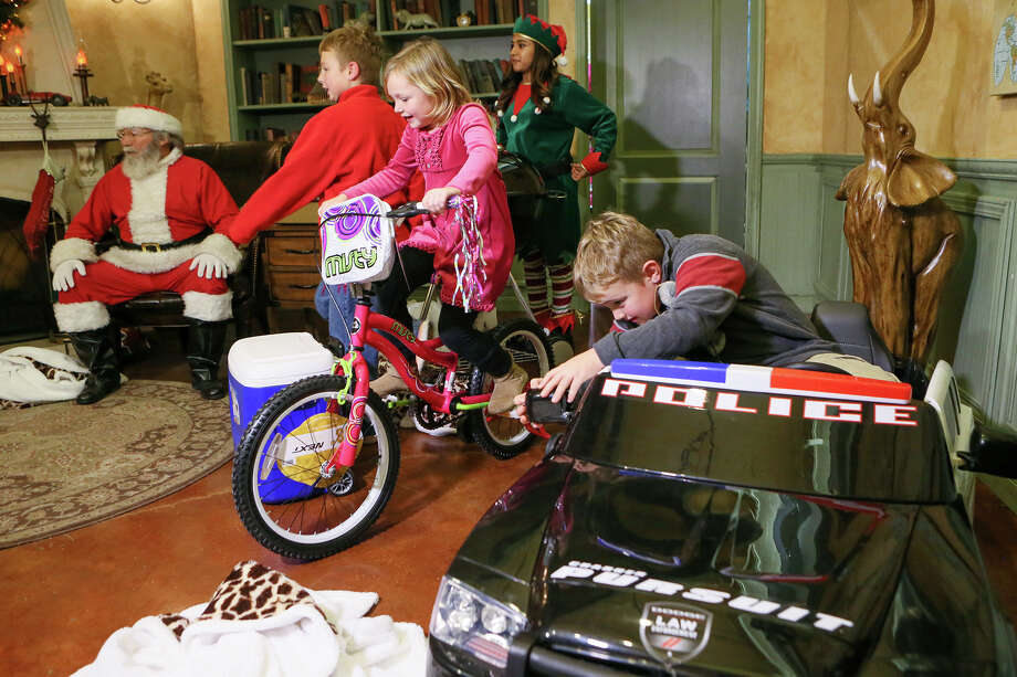 """Hudson Huffman (from right), 8, checks out his new car while his sister Alivia, 6, rides her bike in front of their brother, Simon, 9, at the San Antonio Zoo on Wednesday, Dec. 23, 2015. The San Antonio Zoo and their young professional group, The Zoomers, helped make the Huffman brothers wishes come true by surprising their father with a grill he's always wanted. They also gave presents to the rest of the family. Hudson, 8, shouted """"this is the best Christmas ever!"""" Photo: Photos By Marvin Pfeiffer /San Antonio Express-News / Express-News 2015"""