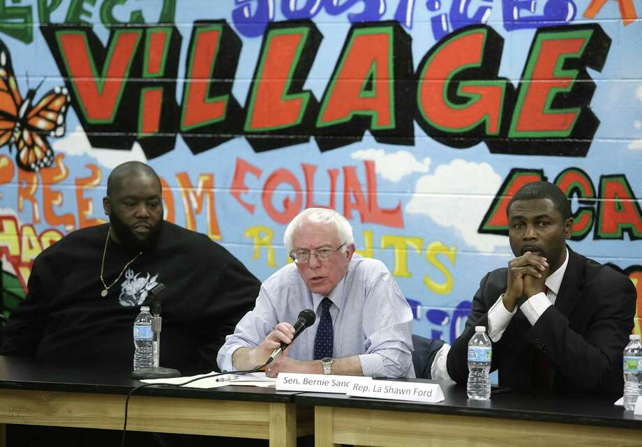 Rapper Killer Mike (left) and state Rep. La Shawn Ford, D-Ill. flank Democratic presidential hopeful Bernie Sanders as he speaks in Chicago  recently about police reform and preventing people of color from being victimized by police officers. Photo: Joshua Lott /Getty Images / 2015 Getty Images