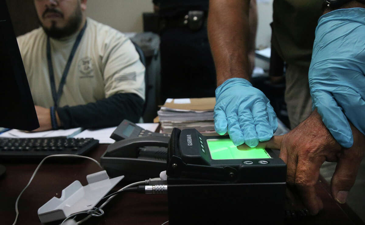 An Immigration and Customs Enforcement (ICE) officer takes finger prints of a prisoner after arresting him (right) Monday August 17, 2015. The agency was conducting a target enforcement operation to round up immigrants with warrants and outstanding deportation orders.