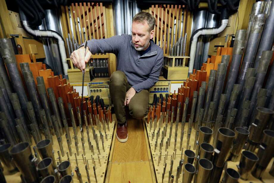 Curtis Bobsin, owner of C. Bobsin Organs, kneels inside one of the compartments as he tunes the pipe organ at Laurel Heights Methodist Church in San Antonio. Photo: WILLIAM LUTHER, Staff / © 2015 San Antonio Express-News