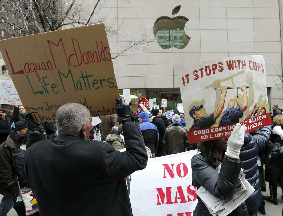 Protesters try to block the entrance to the Apple Store on Chicago's Magnificent Mile, calling for the resignation of Mayor Rahm Emanuel, Thursday, Dec. 24, 2015, in Chicago. The Christmas Eve protest is the latest in a series of demonstrations in the city since the release last month of police video showing a white officer shooting a black teenager 16 times. (AP Photo/Charles Rex Arbogast) Photo: Charles Rex Arbogast, STF / AP