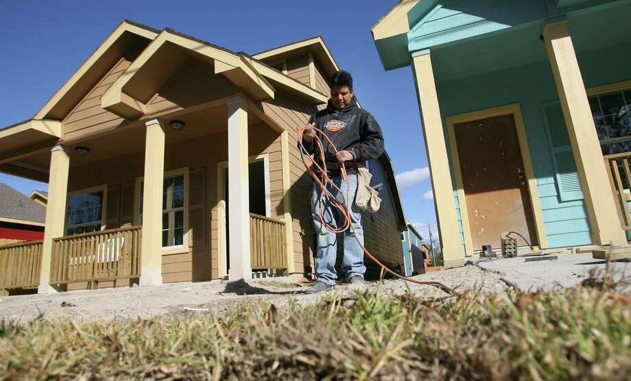 Pablo Bautista works outside a completed Avenue Villa home on Houston's Near Northside, which was part of the city's urban redevelopment program in 2008. Photo: Mayra Beltran, Staff / Houston Chronicle