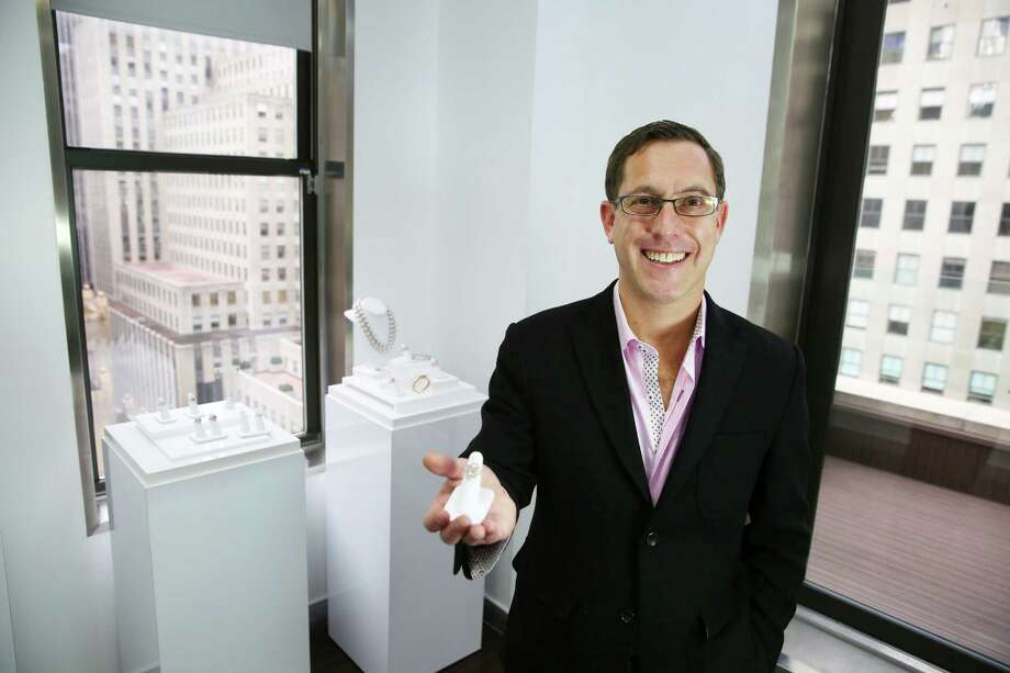 Jordan Fine, a diamond dealer, holds a rare, colored diamond from the 2008 Argyle tender, with a retail price of $1.9 million at JFine Inc., in New York. Dealers say wealthy buyers in volatile economies view rare, colored diamonds as a hedge against economic uncertainty. The value of certain colored diamonds has increased while traditional white diamonds have fallen. Photo: Chang W. Lee /New York Times / NYTNS