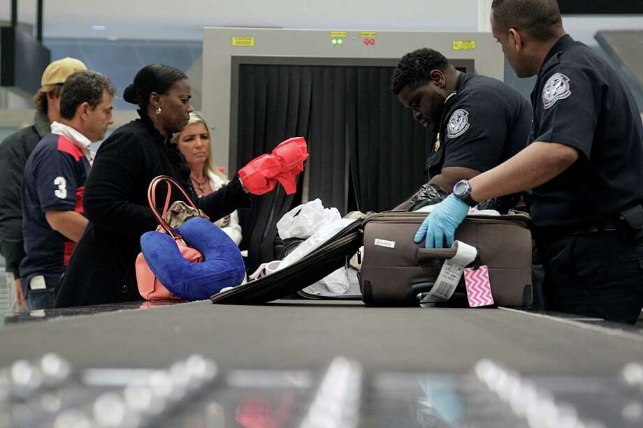 U.S. Customs and Border Protection Agriculture Specialists inspect luggage for prohibited food items at Bush Intercontinental Airport this month. Photo: James Nielsen / Houston Chronicle / © 2015  Houston Chronicle