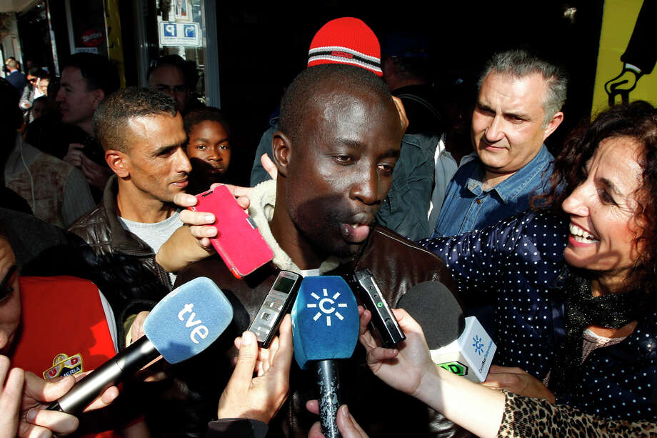 In this Tuesday, Dec. 22, 2015 picture, a Senegalese man named Ngame, who told reporters that he was rescued by Spain's coast guard traveling from Africa's western coast toward Spain's Canary Islands, speaks after discovering he won euro400,000 ($438,000) in Roquetas de Mar, in Almeria province, Spain. About 35 African migrants, including at least one rescued at sea from an overcrowded wooden boat, are among the top prize winners of Spain's Christmas lottery, according to the owner of the lottery agency that sold more than 1,000 tickets worth 400,000 euros ($438,000) each. (AP Photo/Javier Alonso) Photo: Javier Alonso, STR / AP
