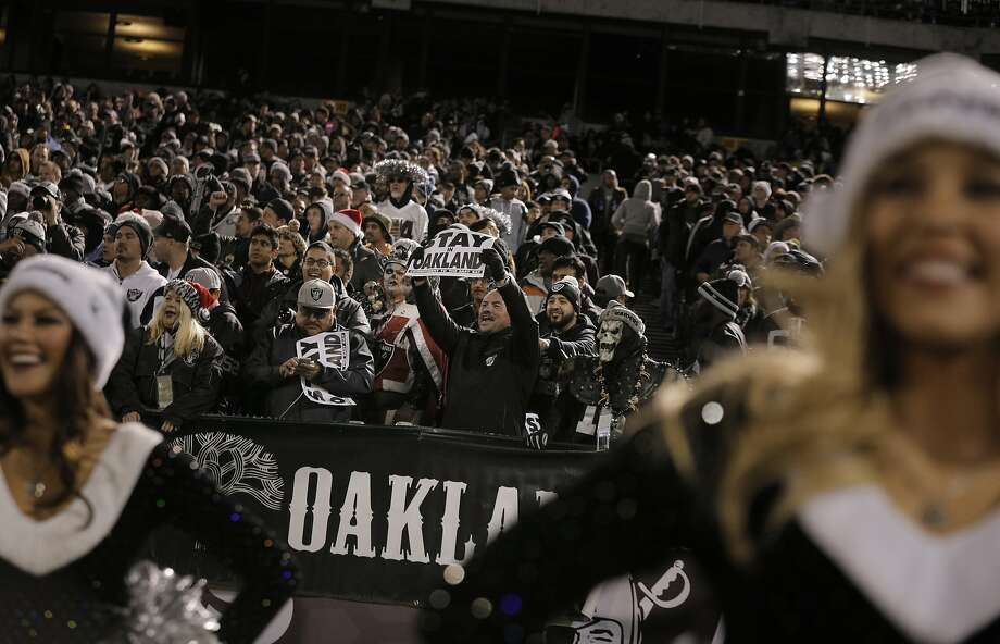 "A Raiders fan holds a sign saying ""Stay in Oakland,"" as the Oakland Raiders played the San Diego Chargers at O.Co Coliseum in Oakland, Calif., on Thursday, December 24, 2015. Photo: Carlos Avila Gonzalez, The Chronicle"