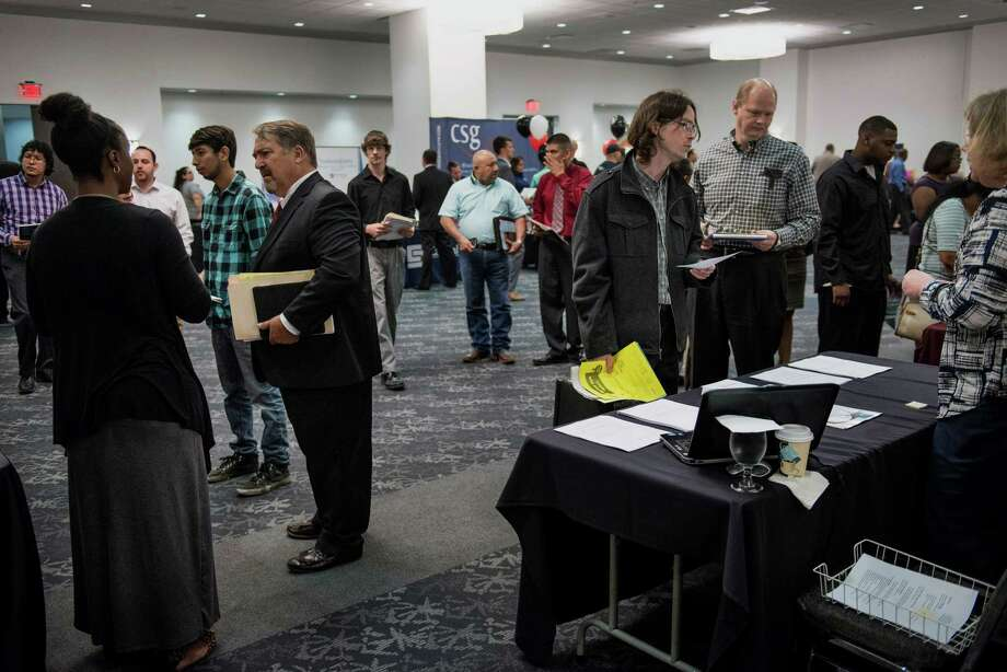 Job seekers speak with representatives at the Choice Career Fair in San Antonio in the spring. Economists generally believe that wage pressures start to heat up when the economy achieves full employment. Photo: Matthew Busch / © 2015 Bloomberg Finance LP