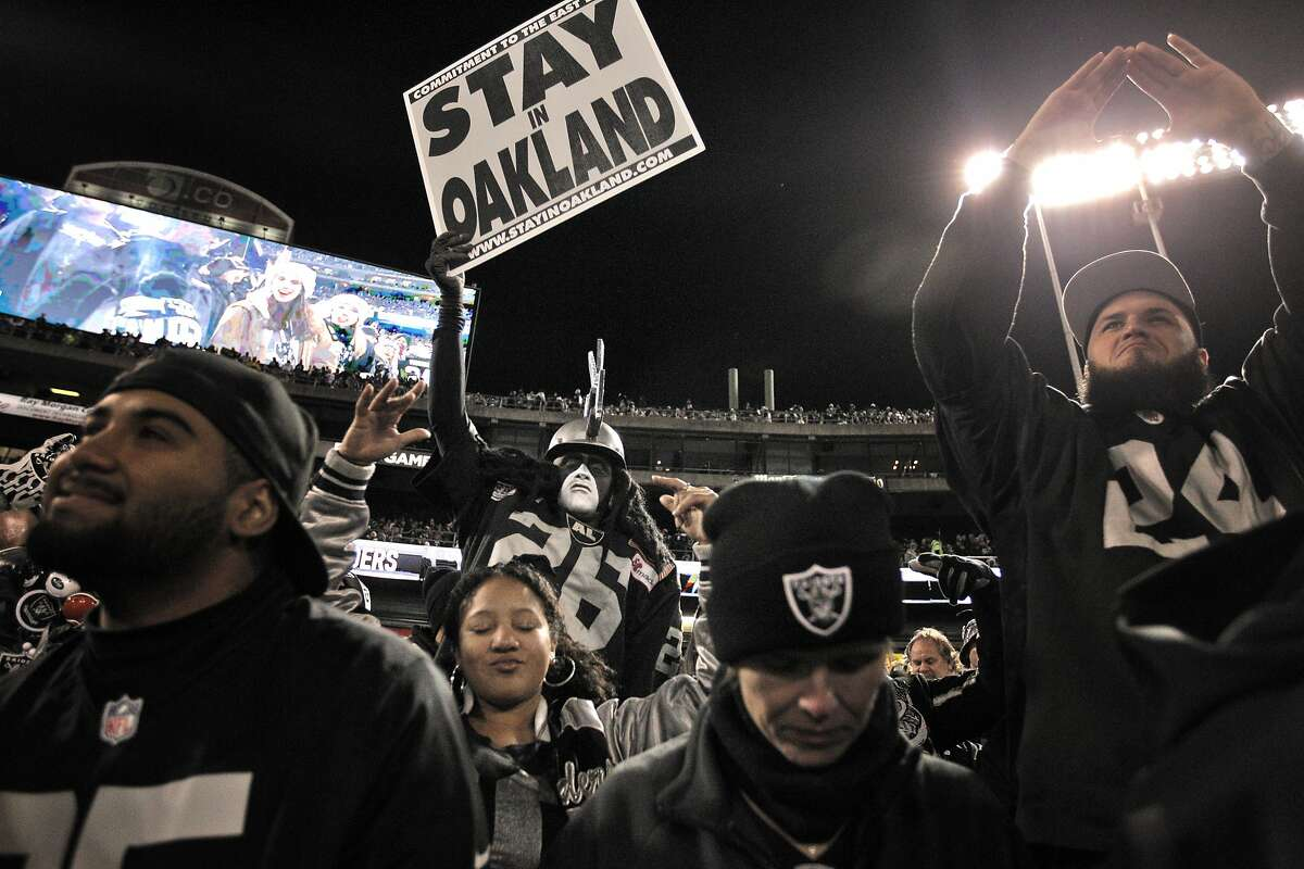Ray Perez dressed as Dr. Death, center, waves a sign for the team to stay while cheering in the Black Hole as the Oakland Raiders played the San Diego Chargers at O.Co Coliseum in Oakland, Calif., on Thursday, December 24, 2015.
