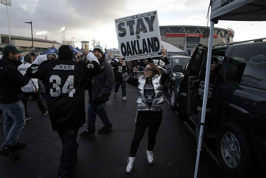 """Felicia Gonzales holds a """"Stay in Oakland"""" sign as other fans pass by in the parking lot before the Oakland Raiders played the San Diego Chargers at O.Co Coliseum in Oakland, Calif., on Thursday, December 24, 2015. Photo: Carlos Avila Gonzalez, The Chronicle"""