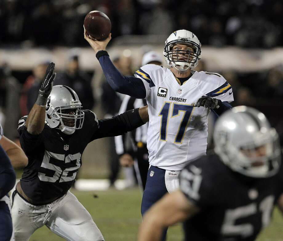 Philip Rivers (17) throws a pass under pressure in the fourth quarter as the Oakland Raiders played the San Diego Chargers at O.Co Coliseum in Oakland, Calif., on Thursday, December 24, 2015. Photo: Carlos Avila Gonzalez, The Chronicle