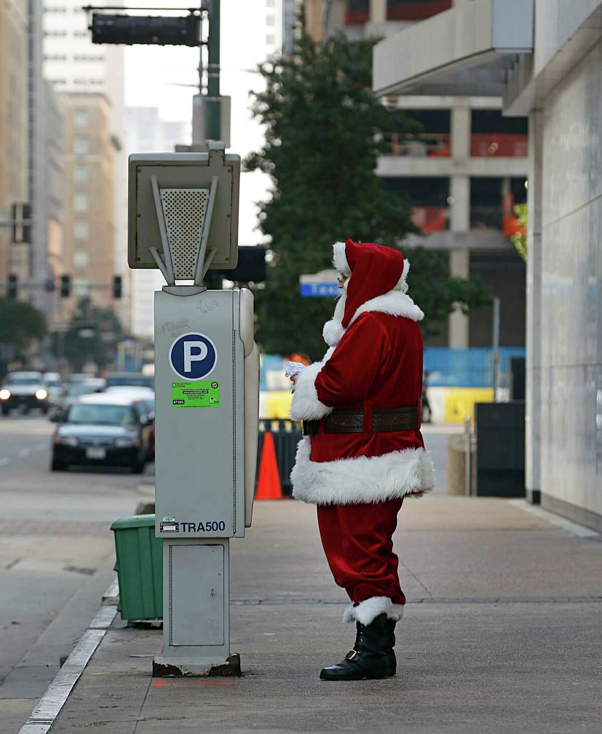 Santa Claus also known as Michael Weinberger uses a parking meter Thursday, Dec. 24, 2015, in Houston.