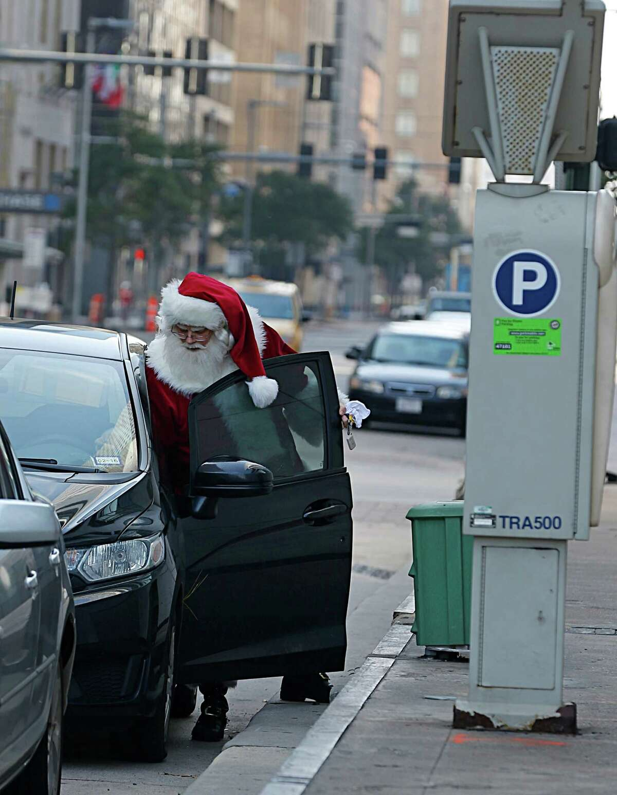 Santa Claus also known as Michael Weinberger palces a parking pay stub in his vehicle Thursday, Dec. 24, 2015, in Houston.