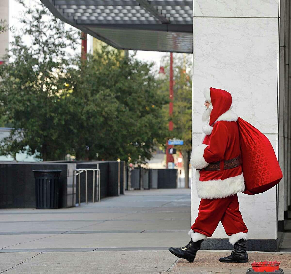 Santa Claus also known as Michael Weinberger walks along Travis street Thursday, Dec. 24, 2015, in Houston.