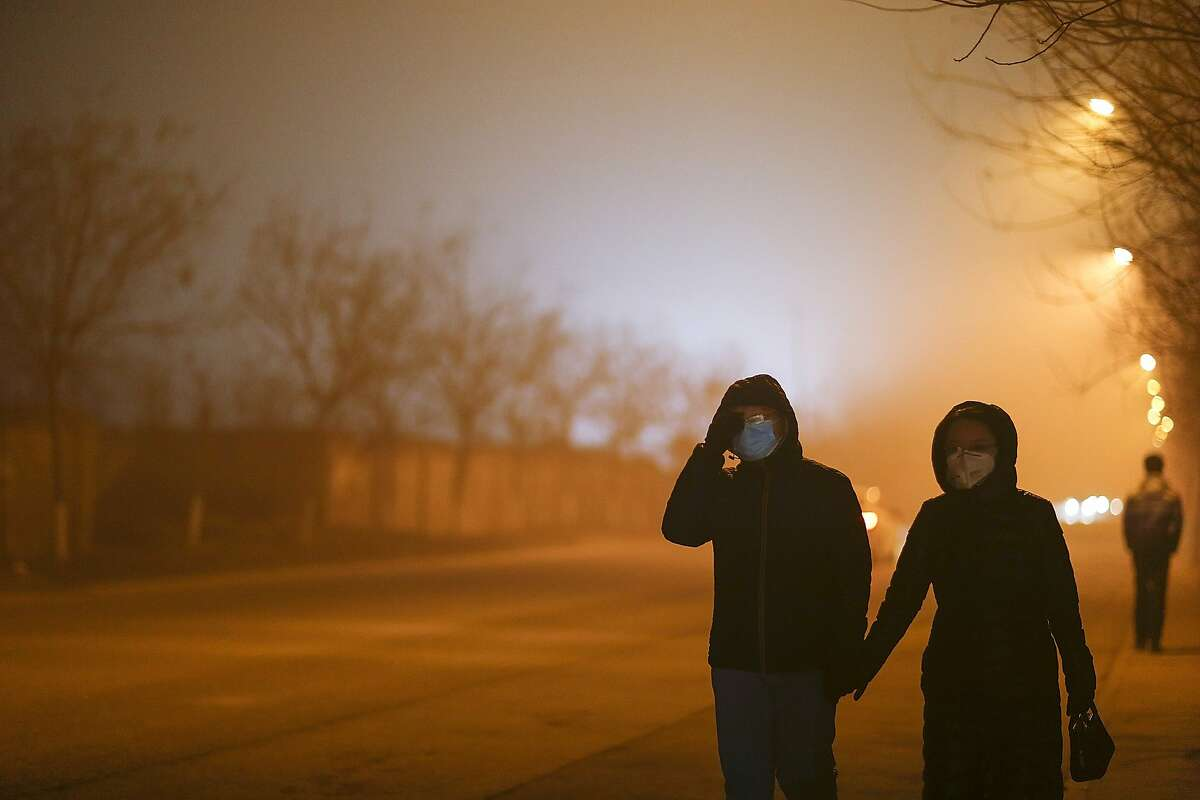 People walk wearing masks on a heavy pollution evening on December 22, 2015 in Beijing, China. Alerts have been issued for air pollution according to the Beijing air pollution emergency management headquarters. Heavy smog has hit China's Beijing-Tianjin-Hebei region on three occasions since late November.
