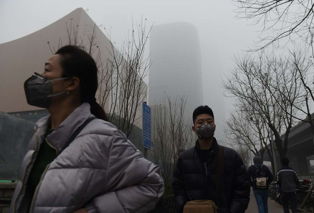 Pedestrians wear masks on a heavily polluted day in Beijing on December 22, 2015. The Chinese capital imposed the highest tier of a four-colour smog warning system for four days starting December 19, the second time the red alert was applied since Beijing established the pollution precaution scheme in 2013.