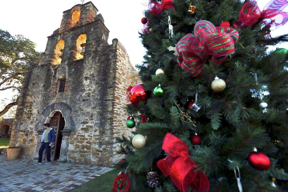 A visitor exits the Christmas decorated Mission Espada church Thursday afternoon, Dec. 3, 2015. Photo: William Luther, Staff / San Antonio Express-News / © 2015 San Antonio Express-News