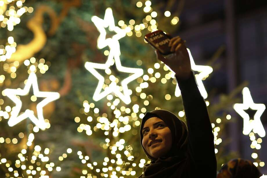 A Muslim Lebanese woman takes a selfie with Christmas trees in Downtown Beirut, Lebanon.  Photo: Hassan Ammar, Associated Press