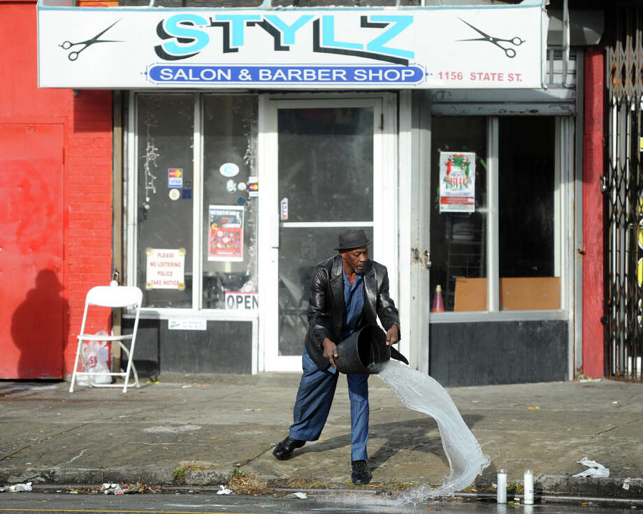 A man who would not identify himself uses a pale of water to wash blood from the gutter in front of Stylz Salon & Barber Shop, on State St., in Bridgeport, Conn. on Christmas morning, Dec. 25, 2015. Police say 14-year-old Luis Colon was apparently caught in the cross fire of adults shooting at one another, and was struck and killed while standing in front of the shop on Christmas Eve. Photo: Ned Gerard, Hearst Connecticut Media / Connecticut Post