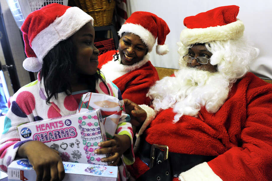 """Bryanna Malcolm, 7, of Bridgeport, greets Santa and Mrs. Claus, played by Larry Harris and Wanda Simmons, after picking up toys at """"Santa's Last Stop"""" in Bridgeport on Friday. Photo: Ned Gerard / Hearst Connecticut Media / Connecticut Post"""
