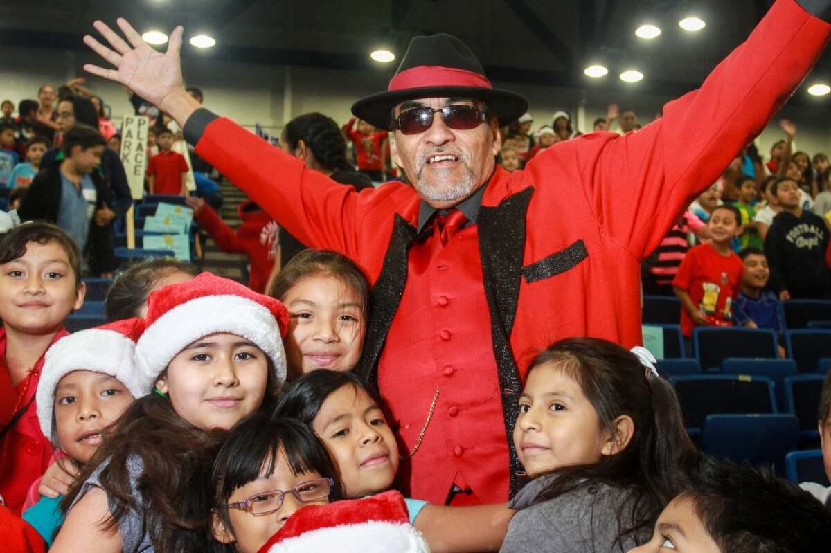 Richard Reyes as Pancho Claus, surrounded by students at the Navidad En El Barrio annual Christmas Program at George R. Brown Convention Center. Over 2,000 children from 50 different elementary schools attend the toy giveaway.