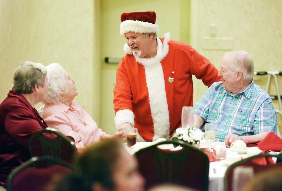 Volunteer Nick Edwards, dressed as Santa Claus, greets Una Frederick, center, 97, and her children Eunice Frederick and John Frederick, of Greenwich, at the annual Christmas community lunch at the Knights of Columbus headquarters in Greenwich, Conn. Friday, Dec. 25, 2015.  About 30 volunteers helped serve 70 local seniors in the headquarters' dining room and about 75 meal home deliveries were made on Christmas Day. Photo: Tyler Sizemore / Hearst Connecticut Media / Greenwich Time