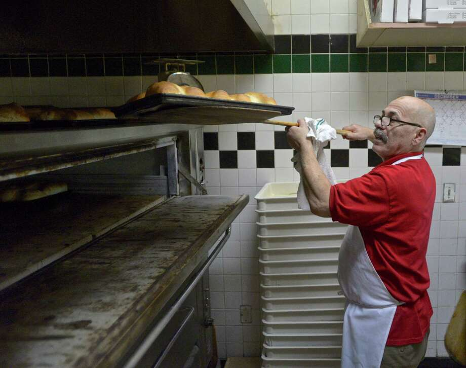 Tony Elmazi pulls loaves of bread from the over for Portofino Restaurant's 20th annual Christmas dinner. The restaurant hosts members of the community for free on Christmas Day. December 25, 2015, in New Fairfield. Photo: H John Voorhees III / Hearst Connecticut Media / The News-Times