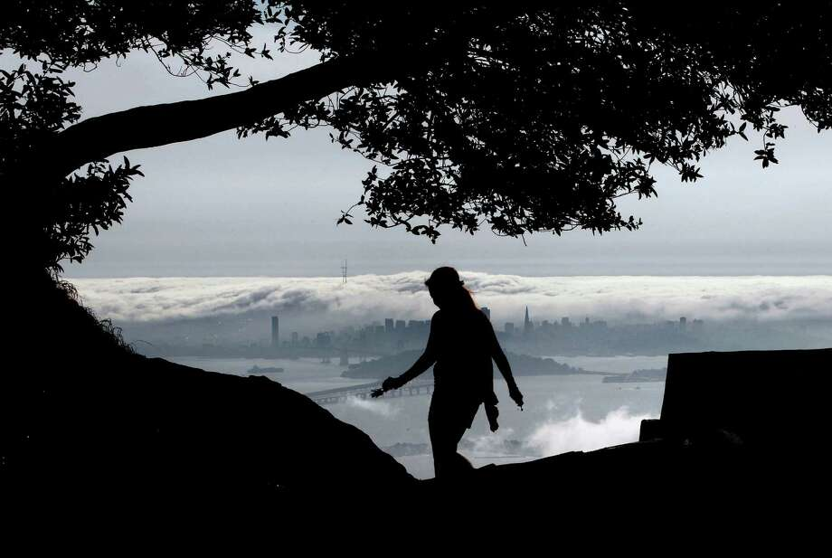 Danielle Roush is silhouetted against a view of fog rolling across the San Francisco skyline and into the bay, as seen from Grizzly Peak Boulevard in Berkeley. Photo: Michael Macor / The Chronicle / ONLINE_YES