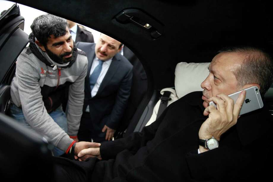 Turkish President Recep Tayyip Erdogan, right, talked Vezir Cakras, left, out of jumping off a bridge Friday, Erdogan's office says. Photo: Yasin Bulbul, POOL / Pool Presidential Press Service