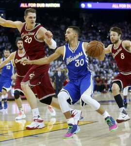 Golden State Warriors' Stephen Curry drives against Cleveland Cavaliers' Timofey Mozgov and Matthew Dellvedova in 2nd quarter during NBA game at Oracle Arena in Oakland, Calif., on Friday, December 25, 2015.