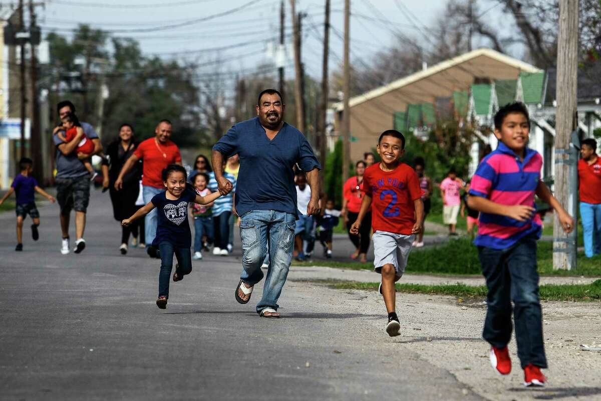 Kids and families run toward a caravan of cars from the Latin Fantasy Lowrider Car Club as they distribute toys and goodie-bags throughout Houston's low-income neighborhoods Friday, Dec. 25, 2015. The club has been delivering toys for 24 years.