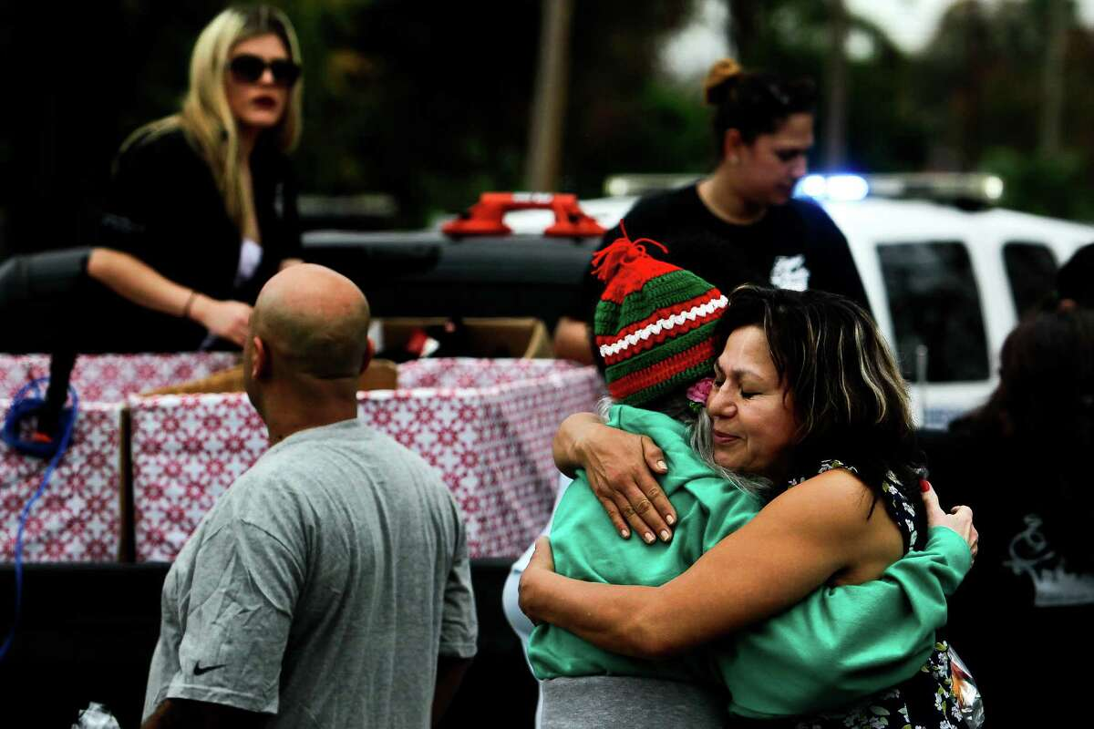 """Rosie Chavila, right, hugs Ann Bandy after they both received Christmas gifts from the Latin Fantasy Lowrider Car Club as they drive through Houston's low-income neighborhoods Friday, Dec. 25, 2015. """"I've never had anything like this before,"""" Bandy said."""