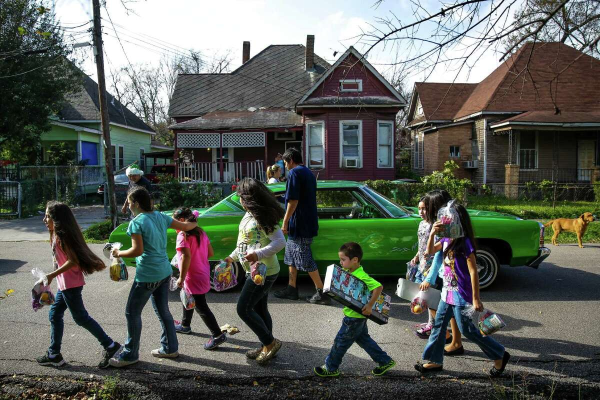 A group of kids walk back to their homes with their new presents from the Latin Fantasy Lowrider Car Club as the club distributes toys and goodie-bags throughout Houston's low-income neighborhoods Friday, Dec. 25, 2015.
