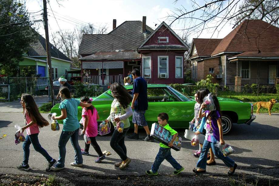 A group of kids walk back to their homes with their new presents from the Latin Fantasy Lowrider Car Club as the club distributes toys and goodie-bags throughout Houston's low-income neighborhoods Friday, Dec. 25, 2015. Photo: Michael Ciaglo, Houston Chronicle / © 2015  Houston Chronicle