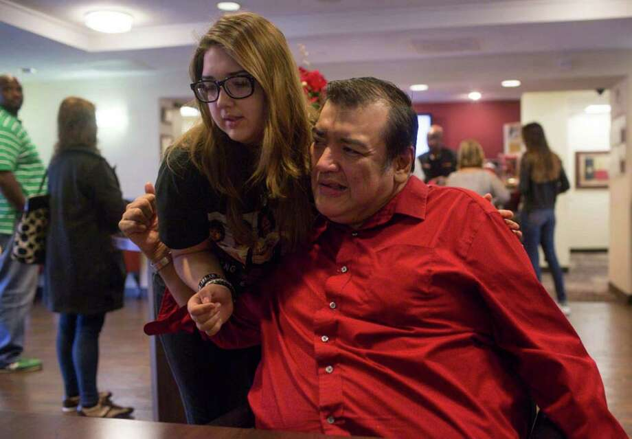 Chris Fonseca, a comedian with cerebral palsy, hugs his daughter Jessica Fonseca, 14, at the Red Roof Inn in downtown San Antonio, Texas on December 25, 2015. Photo: Carolyn Van Houten, San Antonio Express-News / San Antonio Express-News / ©2015 San Antonio Express-News