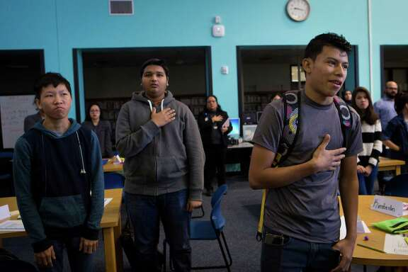 Antony Melendez, right, 16, puts his hand on his heart participating in the pledge of allegiance at Cesar E. Chavez High School along with other newcomers Adhvaryu Bhuvin, center, 17, and Trung Ngo, left, 17, on Dec. 3. ( Marie D. De Jesus / Houston Chronicle )